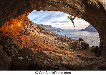 Male rock climber climbing along a roof in a cave