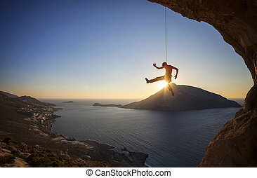 Male rock climber falling of a cliff at sunset