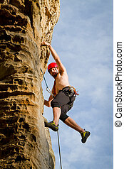 male rock climber - male climbing on sandstone cliff