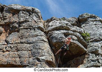 Male Rock Climber - Male rock climber ascending steep climb