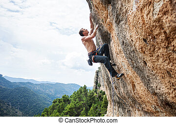 Male rock climber on challenging route on cliff