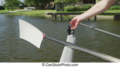 Male rower fixing the oar on the boat - Close up detail of a...