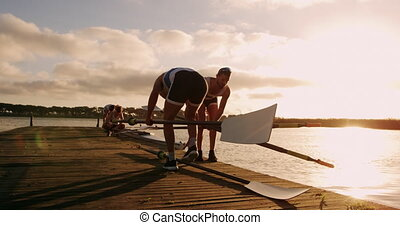 Male rower holding oars on jetty - Rear view close up of two...