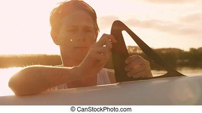 Male rower preparing boat before practice - Front view of a ...