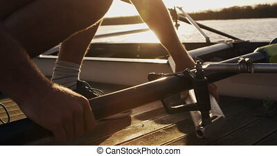 Male rower preparing boat before practice - Side view close ...