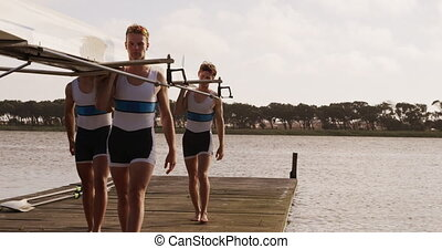Male rower team carrying the boat on their shoulders - Front...