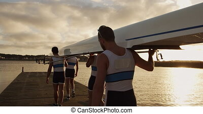 Male rower team carrying the boat on their shoulders - Rear ...