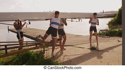 Male rower team carrying the boat on their shoulders - Side ...