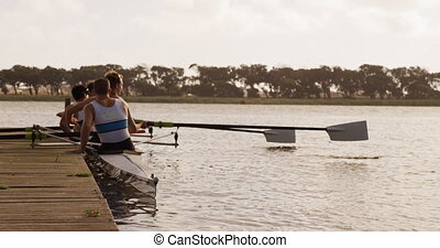 Male rower team getting ready to practice rowing on lake - ...
