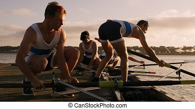 Male rower team preparing for training - Side view of four ...