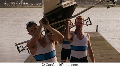 Male rower team putting the boat on their shoulders - Side ...