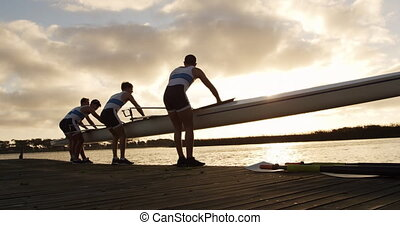 Rear view of four Caucasian male rowers, standing in a row on a jetty, holding a boat, taking it out of the water, holding it above their heads bottom up, during a sunset, in slow motion