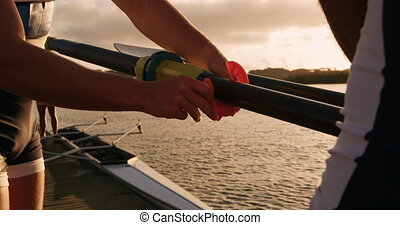 Male rowers fixing the oar - Side view close up of two ...
