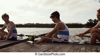 Male rowers laughing on the boat after practice - Side view ...
