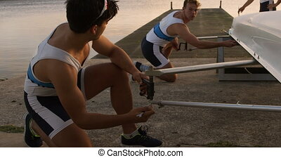Male rowers preparing the boat before practice - Side view ...