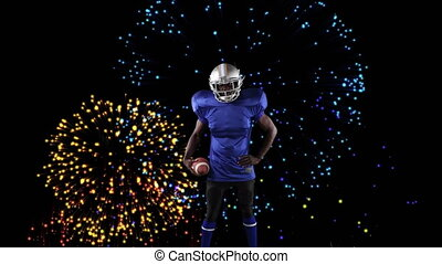 Male rugby player against fireworks in backgroundDigital composite video of Male rugby player holdi