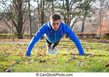 Male Runner Doing Push Up on the Green Lawn in the Park in Sunny Autumn Morning. Healthy Lifestyle and Sport Concept.