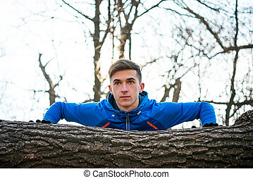 Male Runner Doing Push Up on the Log in the Park in Sunny Autumn Morning. Healthy Lifestyle and Sport Concept.