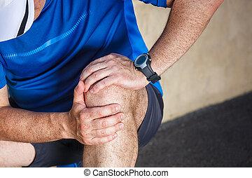 Male runner having problems in knee joint.