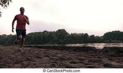 Male runner in red tshirt running along sandy riverside. Super slow motion steadicam shot