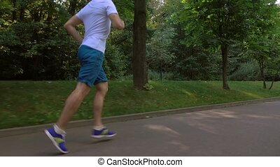 Male runner in white tshirt running in the park. 4K steadicam tracking video