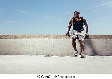 Male runner relaxing on embankment looking away copyspace -...
