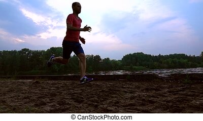 Male runner running along sandy riverside in the evening. Super slow motion steadicam video