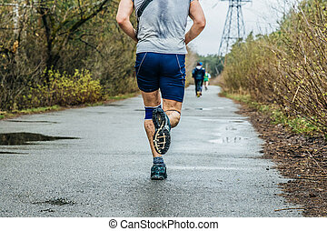 male runner running on asphalt road