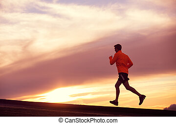 Male runner silhouette, running into sunset