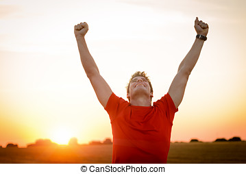 Male runner success - Successful man raising arms after...