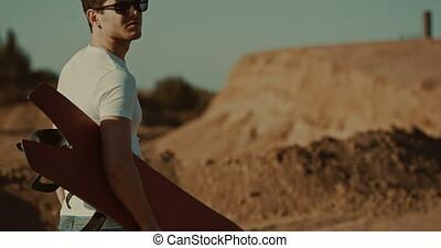 male sandboarder in desert dunes - Tourists Sand Skiing In...