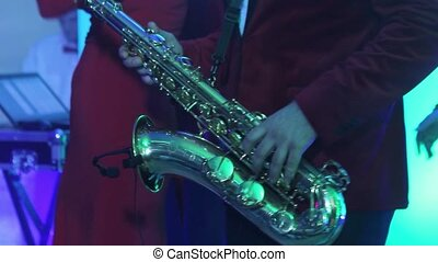 Male saxophonist with a musical band playing on stage in a...