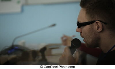 Male says into microphone, adjusts his black sunglasses on his nose.