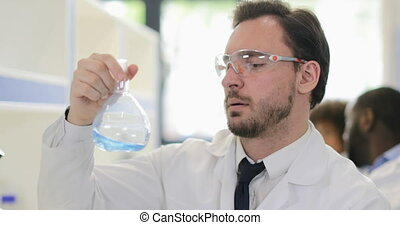 Male Scientist Analyzing Smell Of Liquid In Flask Working In...