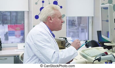 Male scientist notes information on clipboard at the...