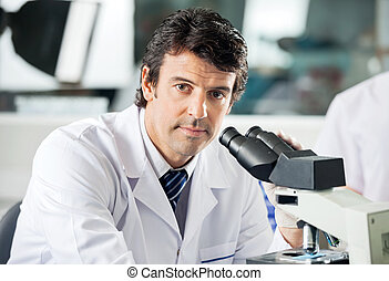 Male Scientist Using Microscope In Lab