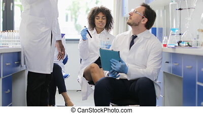 Male Scientists Discussing Experiment Wearing Coats And...