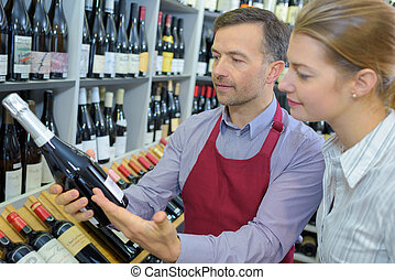 male seller showing bottle of wine to female customer