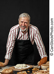 Male senior chef isolated on black background