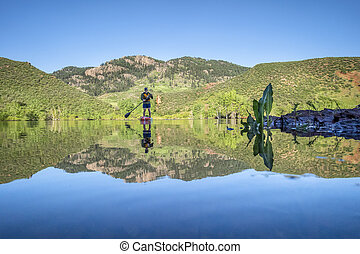 male senior paddler on a stand up paddleboard  in Colorado...