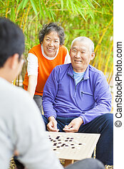 "male seniors win a chinese board game .""weiqi"""