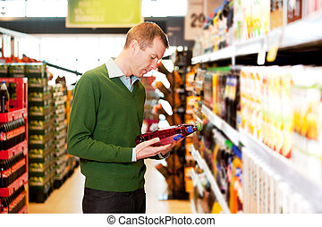 A male shopper in a grocery store comparing products