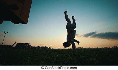 Male silhouette at sunset, capoeira dance on the grass,...
