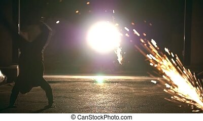 Male silhouette performs flips among the sparks from grinder...