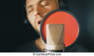 Male singer in headphones singing in sound studio. Young man emotionally recording new song. Guy sings to microphone. Working of creative musician. Show business concept. Slow motion Close up