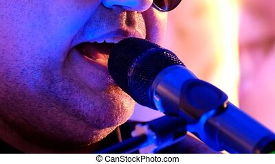 Male singer sings microphone close-up