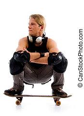 male sitting on skate board