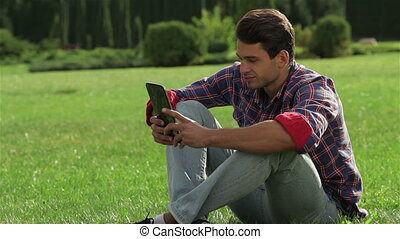 Male sitting on the grass using a tablet