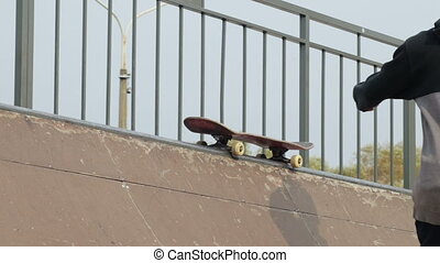 Male skater takes a skateboard from top of ramp and go,...