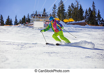 Male skier carving turn on mountain slope, chairlift in...